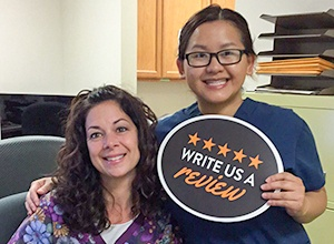 Dental team members smiling and holding a write a review sign