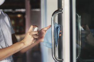 dental team member disinfecting practice door for patient safety