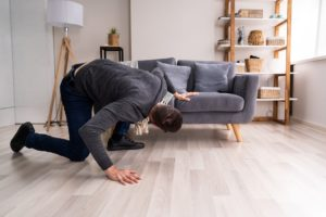 Man searching under sofa for lost Invisalign aligner