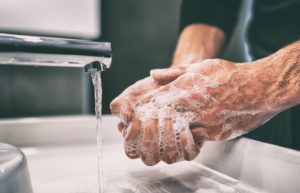Man washing hands before handling Invisalign in Enfield