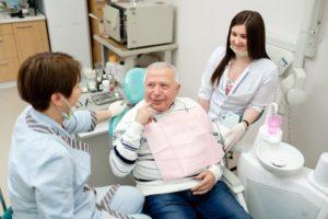 Elderly man visiting dentist for seniors in Enfield
